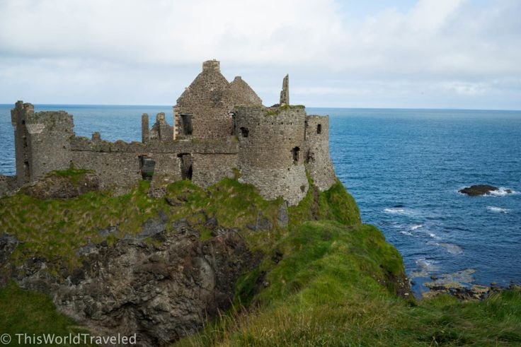 The ruins of the once medieval Dunluce castle perched atop the steep cliff in Northern Ireland