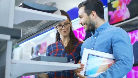 Beautiful Young Couple in the Electronics Store Browsing, Looking for Newest Gadgets