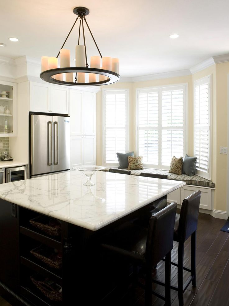 This Neutral Transitional Kitchen Features A Dark Wood Island With A Marble  Countertop And Leather Barstools. A Round Chandelier With Pillar Candles  Hangs ...