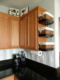 Increase kitchen storage ideas by adding narrow open shelving to hold baskets to organise different categories in the kitchen