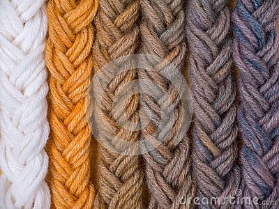 Braided wool yarn swatches colored by henna and indigo mix in different proportions and control white sample