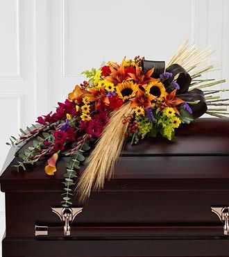 The FTD® Glorious Garden™ Casket Spray has a sweeping look that will add to the elegance and sophistication of their final farewell service. Burgundy gladiolus, orange Asiatic lilies, orange mini call