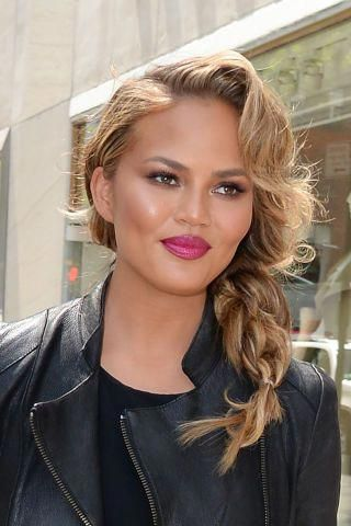 Chrissy Teigen Chrissy Teigen dresses up her all-black biker ensemble with a loose side braid, a wavy fringe, and a berry-colored lip. #sideBraided