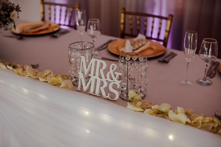 Monte Vista Venue Mr and Mrs sign on the main table for a white and gold wedding with crystal lampshades, glass rose bowls and rose petals