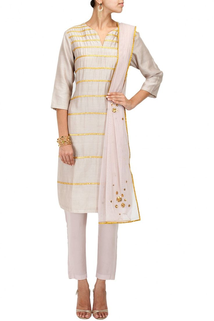 Priyal Prakash | This kurta set features a fawn colour silk chanderi kurta with gold gota striped detailing and matching crepe cropped pants.  It is paired fawn net dupatta with sequins bead embroidered floral motifs and gota border.  COMPOSITION: Silk chanderi, crepe, net. Lining: Cotton.