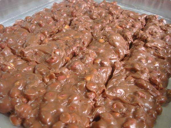 1/2kg de amendoim  1 lata de leite condensado  2 xícaras (chá) de açúcar  2 colheres de chocolate em pó  1 colher (sopa) de margarina ou manteiga  MODO DE PREPARO:  Coloque em uma panela o amendoim com o açúcar, deixando queimar o açúcar por igual até derreter totalmente.  Acrescente o leite condensado, a margarina e o chocolate, mexa até aparecer o fundo da panela.  Depois de desligar o fogo mexa mais um pouco.  Despeje em uma pedra mármore untada com margarina.  Corte ainda morno.