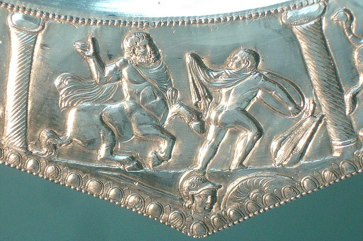 Chiron unterrichtet Achilles im Diskuswerfen. Der Riesendiskus des späteren Helden ist so groß, dass er bis unter die Achsel reicht. Zuvor hat Achilles wohl auf der (rechts) abgelegten Leier gespielt