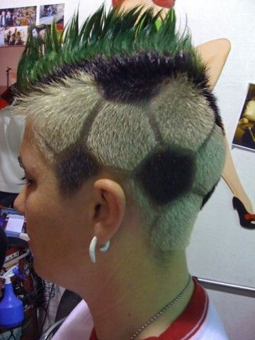 Ladies soccer hair style. Ball on grass.
