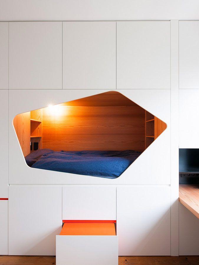 Ingebouwd bed in witte kast met oranje accenten.