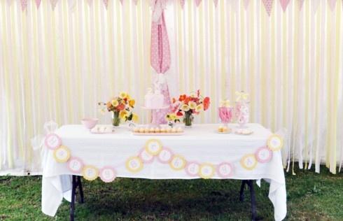 Corrente de doily + scrap redondo na mesa bolo. Fundo de fitas de cetim largas rosa, palha e laranja claro com bandeirolas scrap
