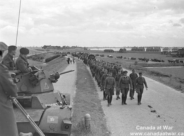 The Netherlands - Canadians escort German prisoners out of Holland.
