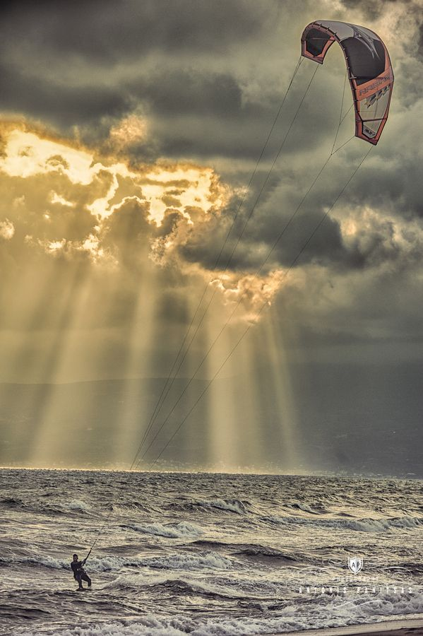 Kite serf by Antonis Panitsas.  sunlight streaming thru the clouds. awesome....