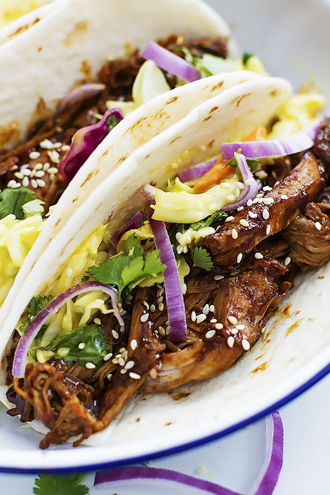 Slow Cooker Korean BBQ Pork Tacos - Juicy slow cooked shredded pork slathered in Korean bbq sauce, topped with creamy slaw, and wrapped in taco shells!