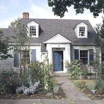 Welcome Home!  The blue door and window shutters are a nice contrast to the white.  What a perfect exterior style for a country cottage home by the sea!