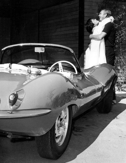 Steve McQueen with wife Neile Adams and his Jag.