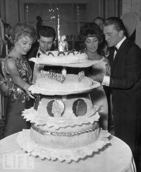 """The Fishers Meet the Douglases  Eddie Fisher and Elizabeth Taylor join Kirk Douglas (right) and his wife Anne Buydens (left) at a party in Rome in January 1961 marking the first anniversary of Douglas' film """"Spartacus."""""""