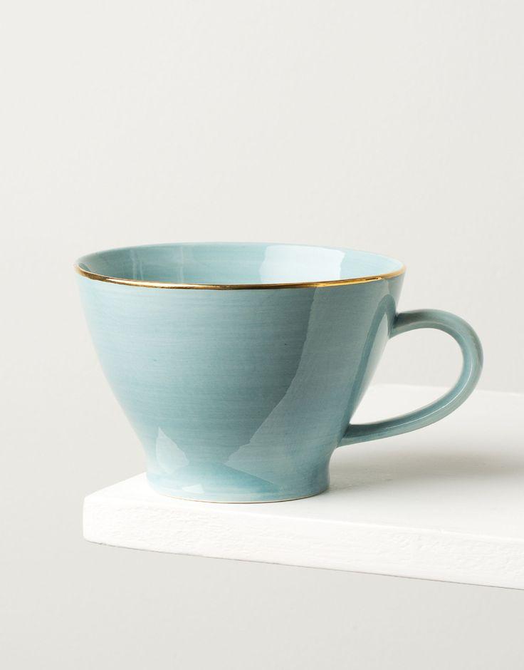 Större mugg i ljusblå ton med en guldfärgad kant.