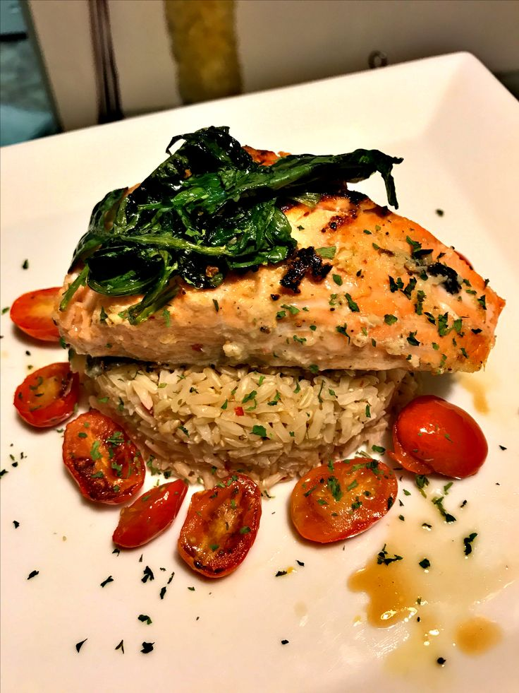 Salmon over rice with roasted tomatoes topped with sautéed spinach
