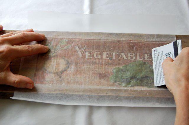 4 Segurando a transferência apertando a  madeira, e trabalhar rapidamente, passe a borda de um cartão  através da imagem. Isso empurra a tinta do papel encerado para dentro da madeira, que absorve.  Não seja covarde sobre isso. Empurrar com firmeza mas não ao ponto de você rasgar o papel encerado.delicadamente o papel para ver se ele está transferindo bem. Se você notar manchas que não tenham transferidos, esfregue-o um pouco mais com o cartão de crédito, de...