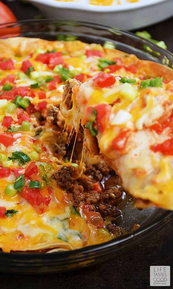 Taco Pie   by Life Tastes Good is an easy and economical recipe perfect for even the busiest nights of the week! Refried beans and seasoned ground beef sandwiched between 2 large flour tortillas is topped with shredded cheese and fresh vegetables to create a Mexican inspired dish the whole family will love! #LTGRecipes