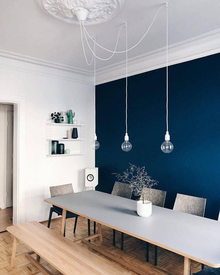 Die dunkelblaue Wandfarbe lässt das Esszimmer von…