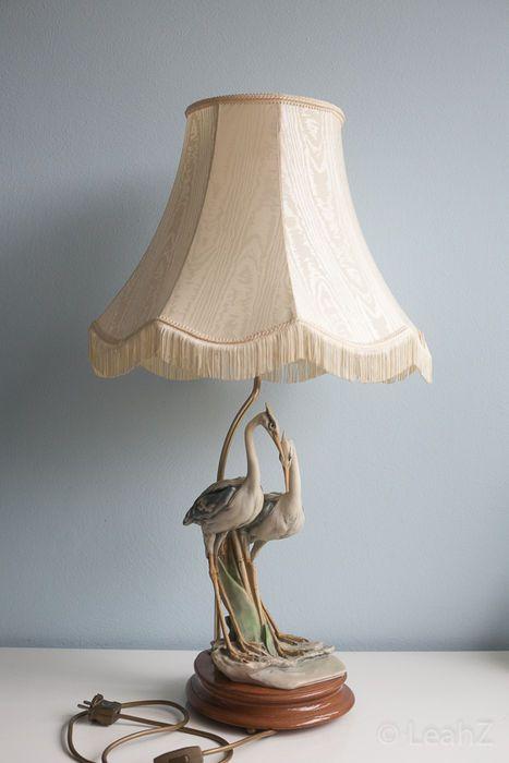 Pennati R. - Tafellamp met porseleinen vogelsculptuur  Tafellamp met handgemaakte sculptuur van twee reigers in bisque porselein. Heeft daardoor een mat oppervlak behalve de ogen. Die zijn van glas (of gepolijste stenen) gemaakt. Deze prachtig gedetailleerde Capodimonte sculptuur staat op een stevige houten voet die voorzien is van een lamp met lampenkap. Hoogte = 79 cm (incl. lampenkap) Hoogte sculptuur = 36 cm Aan de onderkant van de staart van één van de vogels is een kleine reparatie…