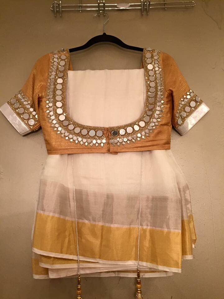 Gold and white saree teamed with a statement blouse with mirrow work on it.