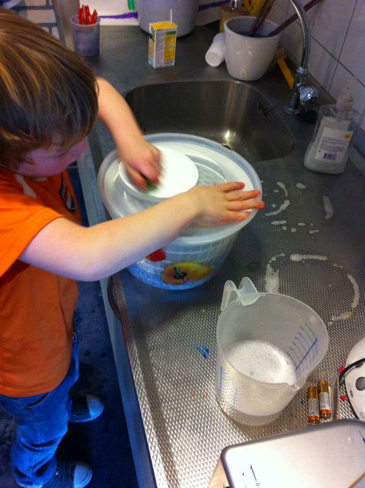 Thema Groter groeien. Babywasje in de (sla)centrifuge. Maatbeker erbij om te meten hoeveel water eruit zo'n wasje komt.