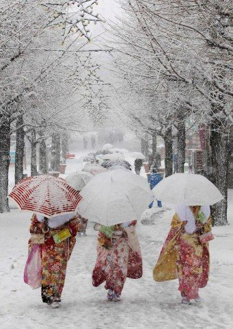 Snow in Tokyo ~ Photo by Yuya Shino — Japanese women in kimonos walk during a heavy snowfall at Toshimaen amusement park in Tokyo. They are attending a ceremony celebrating Coming of Age Day in which youths across Japan are honoured when they reach the age of 20.