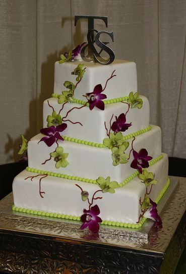 Four tier white square wedding cake with green beads and silver monogram toppers.JPG