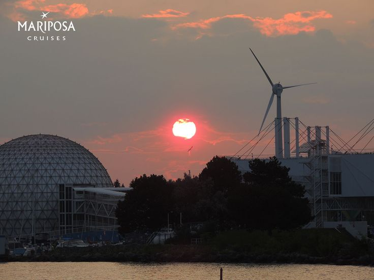 The sun sets between the Ontario Place Cinesphere and the Toronto WindShare ExPlace turbine.