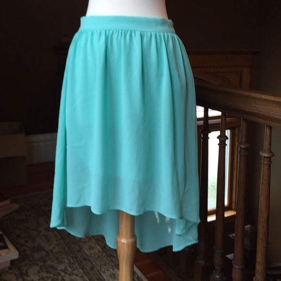 "Forever 21 mint green skirt Skirt, zips up the side. Longer in back than front. Sheer but lined. 100% polyester. Skirt length in front, waist to hem is 18"". Mint green color. Excellent condition. Forever 21 Skirts Asymmetrical"