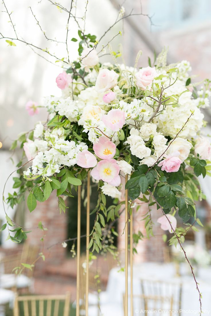 large wedding reception arrangement of white hydrangea, white o'hara rose, sweet akito rose, white stock, spirea, white majolik spray rose, light pink ranunculus, light pink parrot tulip, & greenery on tall modern gold pedestal.