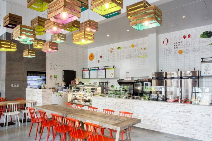 Painted wooden crates serve as lighting features and brand recognition factor and white brick walls featuring rough wooden surfaces deliver a farm-like feel that invites customers to enjoy healthy and safe food in a welcoming environment.
