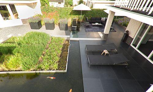 Moderne #achtertuin met #ligbedden, een #vijver, #bloembakken, #siergrassen en veel details: loopbrug van glas waaronder de vissen zwemmen, de watertafel en de RVS lijn die in het terras loopt, langs de brug gaat en daar verhoogd de border vormt en eindigt onder de overkapping (buiten beeld). #Design tuin | Heart for Gardens.