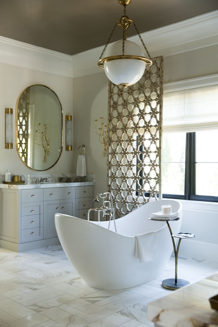 The master bathroom is equally as elegant. I mean…let's talk about those marble floors, metallic ceiling, and french gray cabinetry. | French Modern Manor Designed by Alice Lane   Tub – Juliet I Tub by MTI Baths | Wall Color – Benjamin Moore Gray Mist | Ceiling Color – Liquapearl (LP1013) by MDC | Flooring – Honed Calacatta Gold by Daltile | Countertops – Butterfly Marble from Italia Marble & Granite