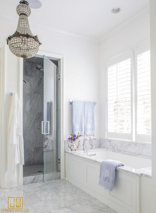 An eye-catching French chandelier hangs over gray marble floor tiles leading to a drop in wainscoted bathtub finished with a gray marble tub deck positioned beneath a window covered in plantation shutters.