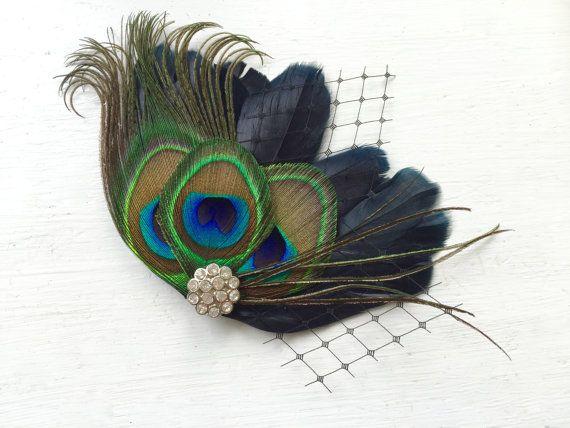 Nuestra inspiración vintage fascinator de MICHELLE es elegante. Hecho de una base de plumas negras de sedosos, una pluma de pavo real natural y volutas naturales, es acentuado por velo ruso negro y joyas de imitación de cristal. Se fija con una pinza. Puede hacer en plumas marfil así o un color diferente de pavo real plumas--mensaje solo me. Perfecta para su gran día.