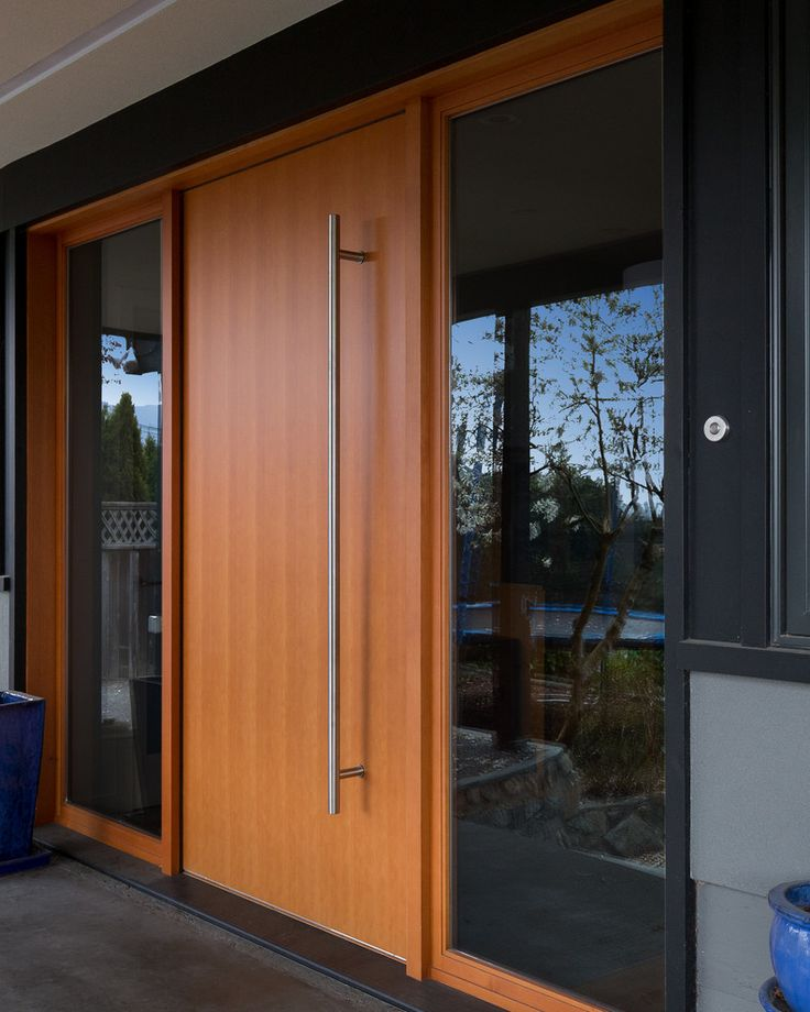 this light wood door features an oversized metal door handle and is flanked by windows on both sides to create a modern entry into this family home
