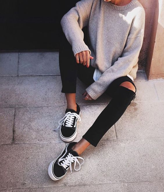 distressed black jeans, a neutral sweater and black chucks