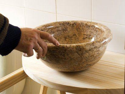 Cuenco de mármol travertino montado sobre encimera de madera