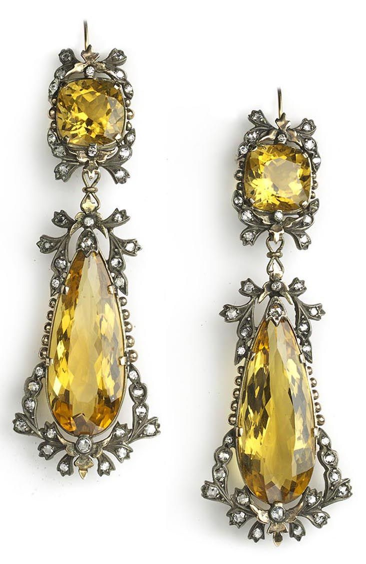 ANTIQUE DIAMOND AND CITRINE DROP EARRINGS. A pair of fine antique diamond and citrine drop earrings, each earring set with a cushion and pear shape citrine within a bow and swag old-cut diamond surround, Mounted in silver on gold. Circa 1880
