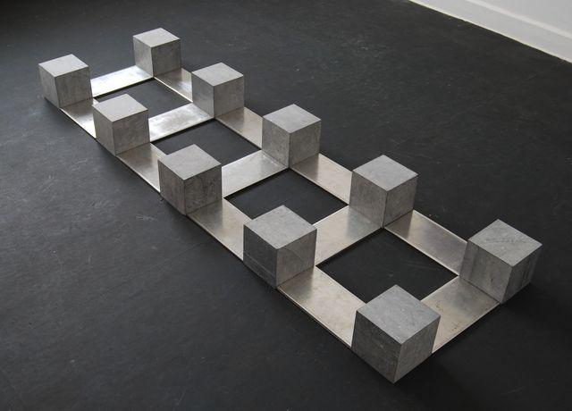 Open/gesloten - Carl Andre- BELGICA TIN Tetraquad, 1990 Materialen: tin, Belgische blauwe kalksteen. Dit werk zou heel zwaar moeten lijken, door de materialen en de geometrische vormen, maar toch voelt het licht aan. Door de afwisseling tussen massieve blokken, open ruimten en dunne platen creëert hij een beeld dat de ruimte vult, maar niet overheerst. De kleuren en materialen geven je op het eerste zicht een stijf gevoel, maar door de fragiel uitziende platen word het op eens zeer buigbaar.