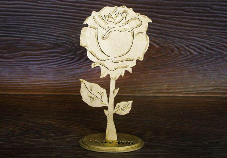 Сувенир на подставке в виде розы выполнен из дерева с помощью лазерной резки. Окрашен краской золотого цвета и акриловым контуром с блесками. На подставке нанесена надпись I LOVE YOU. Роза имеет высоту 17 см и ширину 9 см. Сувенир можно преподнести подруге или жене на День всех влюбленных, на Международный женский день или на День рождения. Роза будет хорошо смотреться на столе или на полке и украшать интерьер помещения. Купить сувенир из дерева оптом или в розницу можно в интернет магазине…