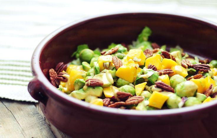Spruitjessalade met mango, avocado, rode ui, pecannoten en een mosterddressing. Verrassend en tegelijk super voedzaam!