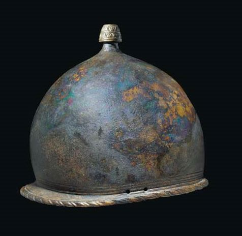 "Montefortino helmet, 3rd century B.C.  The crown topped by foliate finial, the narrow rear peak with hatched triangular motif and 'rope' border extending around the helmet perimeter, ""VII S"" incised on the underside, 21.6 cm high. Private collection, from Christie's auction"