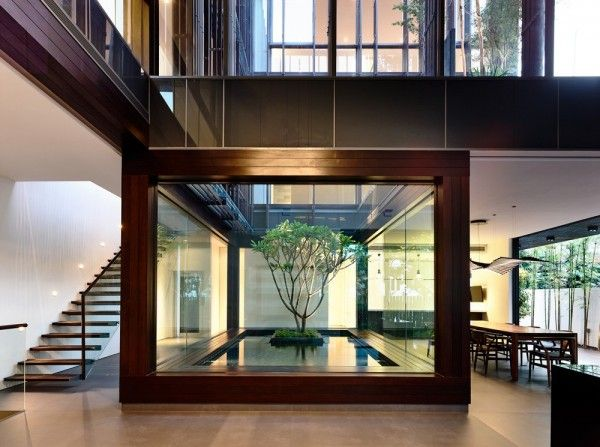 """One of the most notable features in this modern home is the interior courtyard. We have featured homes with stunning courtyard elements before, but this one is no less impressive. It's two story height allows it to be enjoyed from almost any space in the home. The architect points out that in addition to the natural light infusion, it """"acts as a buffer against noise from a major road a distance away."""" Of course, it is also just plainly beautiful with its frangipani tree and small pond."""