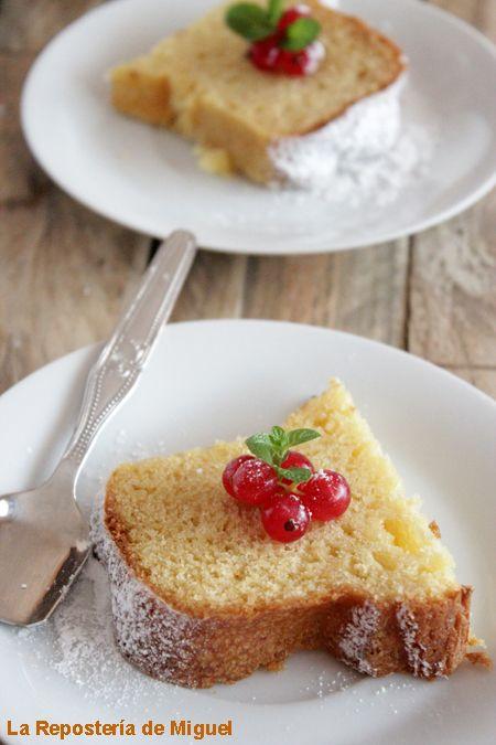 Una porción de bizcocho sobre un plato blanco, la porción de bizcocho esta decorada con un ramillete de grosellas rojas y azúcar glass.