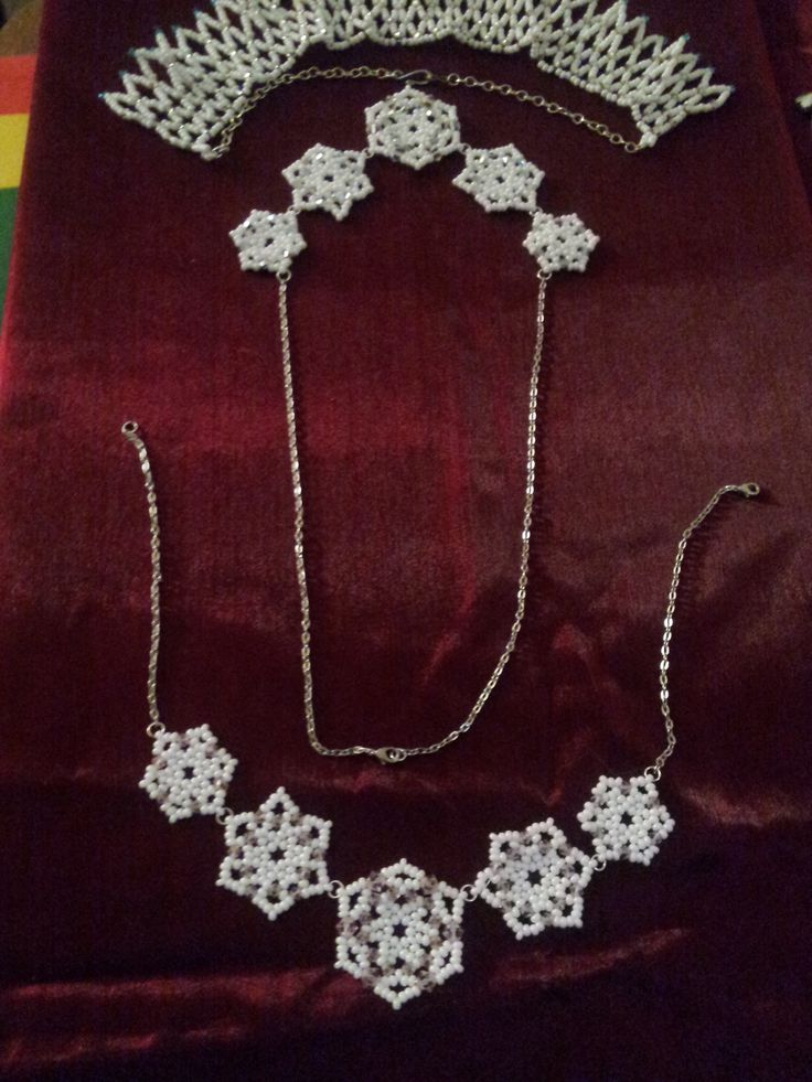 Two versions of a snowflake necklace with Swarovski crystal accents, and a netted collar necklace.
