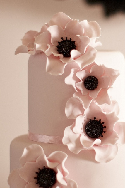 Three tier wedding cake covered in pale pink fondant, and decorated with pale pink anenomes with black glitter centres ...so pretty!!